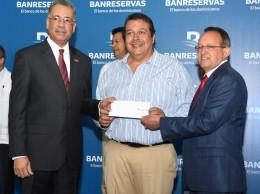 Manuel Tavárez Mirabal, presidente Briquetas Nacionales, recibe cheque de Simón Lizardo y Ángel Estévez.