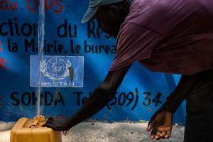 Un residente en el pueblo haitiano de Merger, a una hora de Puerto Príncipe, llena su garrafa en un punto de distribución de agua impulsado por la ONU.