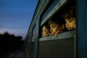 En Macedonia, tres niños miran por la ventana de un tren, que traslada a refugiados de Siria, Afganistán e Iraq a un centro de recepción para migrantes y refugiados.