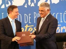 El procurador Jean Rodríguez y el canciller Miguel Vargas reciben el memorando.
